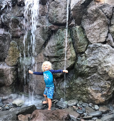 St Kitts Adventurous young boy enjoying the boulder water wall and waterfall shower